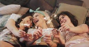 Οι όμορφες νέες γυναίκες στις πυτζάμες που καθορίζουν στο κρεβάτι και τη χρησιμοποίηση τα λαμπιρίζοντας πυροτεχνήματα παίρνουν πε φιλμ μικρού μήκους