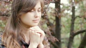 Οι όμορφες νέες στροφές γυναικών στο Θεό με τα συναισθήματα στην προσευχή, το κορίτσι δίπλωσαν τα όπλα της στο στήθος της και με  απόθεμα βίντεο