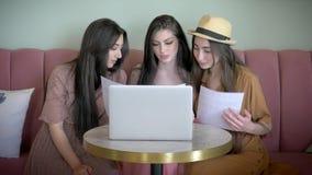 Οι όμορφες φίλες έχουν τη διασκέδαση να φανεί αφίσα διαφήμισης και να επιλέξει το νέο ένδυμα στο σε απευθείας σύνδεση κατάστημα κ απόθεμα βίντεο
