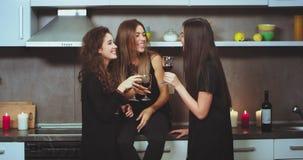 Οι όμορφες χαρισματικές νέες γυναίκες που ξοδεύουν έναν καλό χρόνο μαζί στο σπίτι έχουν ένα λίγο κόμμα κρασιού, στην κουζίνα αυτο απόθεμα βίντεο