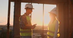 Οι όμορφοι εργαζόμενοι ανδρών και γυναικών κατασκευής στα προστατευτικές κράνη και τις φανέλλες τινάζουν τα χέρια εργαζόμενοι φιλμ μικρού μήκους