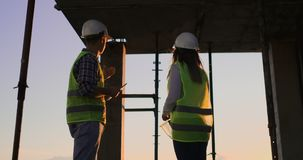 Οι όμορφοι εργαζόμενοι ανδρών και γυναικών κατασκευής στα προστατευτικές κράνη και τις φανέλλες τινάζουν τα χέρια εργαζόμενοι απόθεμα βίντεο