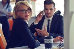 Οι όμορφοι νέοι συνέταιροι χρησιμοποιούν ένα lap-top, συζητούν τα έγγραφα και χαμογελούν εργαζόμενος στην αρχή Στοκ Φωτογραφία