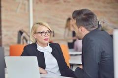 Οι όμορφοι νέοι συνέταιροι χρησιμοποιούν ένα lap-top, συζητούν τα έγγραφα και χαμογελούν εργαζόμενος στην αρχή Στοκ Εικόνες