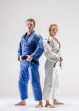 Οι δύο μαχητές judokas που θέτουν σε γκρίζο Στοκ Φωτογραφίες