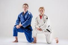 Οι δύο μαχητές judokas που θέτουν σε γκρίζο Στοκ φωτογραφία με δικαίωμα ελεύθερης χρήσης