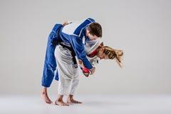 Οι δύο μαχητές judokas που θέτουν σε γκρίζο Στοκ εικόνες με δικαίωμα ελεύθερης χρήσης