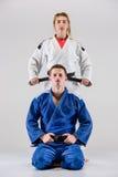 Οι δύο μαχητές judokas που θέτουν σε γκρίζο Στοκ Εικόνες