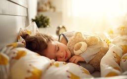 Οι ύπνοι κοριτσιών παιδιών στο κρεβάτι της με το παιχνίδι teddy αντέχουν το πρωί Στοκ Εικόνα