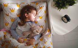 Οι ύπνοι κοριτσιών παιδιών στο κρεβάτι της με το παιχνίδι teddy αντέχουν το πρωί Στοκ Εικόνες