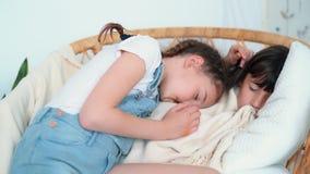 Οι ύπνοι κοριτσιών στην καρέκλα, αδελφή χαϊδεύουν την και κοιμισμένο επόμενο πτώσεων, σε αργή κίνηση απόθεμα βίντεο