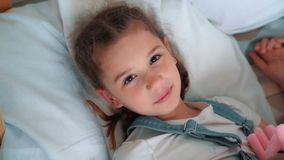 Οι ύπνοι μικρών κοριτσιών γλυκά στο κρεβάτι, ίχνη επάνω και εξετάζουν τη κάμερα, σε αργή κίνηση φιλμ μικρού μήκους