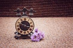 Οι ώρες αναμνηστικών σε ένα υπόβαθρο μπεζ-καφετί burlap στέκονται έπειτα στοκ φωτογραφίες