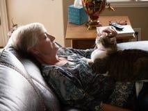 Οι ώριμες γυναίκες χαλαρώνουν καθώς αυτή κατοικίδια ζώα η γάτα της στοκ εικόνες