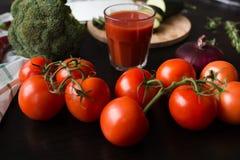 Οι ώριμες κόκκινες ντομάτες βρίσκονται σε έναν μαύρο μοντέρνο πίνακα στο υπόβαθρο βλέπουμε ένα ποτήρι του χυμού ντοματών, κόκκινα στοκ εικόνες με δικαίωμα ελεύθερης χρήσης