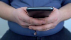 Οκνηρά παχιά παίζοντας παιχνίδια ατόμων στο smartphone, κουβεντιάζοντας φίλοι, στατικός τρόπος ζωής στοκ εικόνα