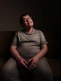 Οκνηρή υπέρβαρη αρσενική συνεδρίαση στον καναπέ και προσοχή κάτι Στοκ εικόνες με δικαίωμα ελεύθερης χρήσης