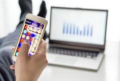 Οκνηρός εργαζόμενος γραφείων που παίζει το κινητό παιχνίδι με το smartphone Στοκ Φωτογραφία