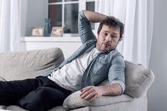 Οκνηρό άτομο που στηρίζεται στον καναπέ αντί της αναζήτησης μιας θέσης εργασίας Στοκ Φωτογραφίες