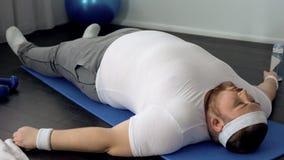 Οκνηρό λίπος που βρίσκεται στο χαλί ικανότητας στο σπίτι, δυσκολίες παχυσαρκίας, αδύνατοι μυ'ες στοκ φωτογραφία με δικαίωμα ελεύθερης χρήσης