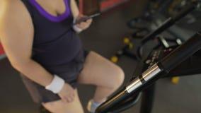 Οκνηρό παχουλό θηλυκό που αργά το στάσιμο ποδήλατο και που τυλίγει στο smartphone απόθεμα βίντεο