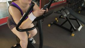 Οκνηρό παχύσαρκο θηλυκό που αργά το στάσιμο ποδήλατο και που τυλίγει στο τηλέφωνο απόθεμα βίντεο