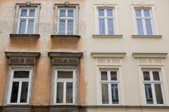 Οκτώ άσπρα παράθυρα στην πρόσοψη των δύο σπιτιών της παλαιάς και νέας στάσης δίπλα-δίπλα Στοκ Εικόνες