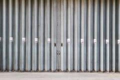 Ολίσθηση και δίπλωμα των βιομηχανικών πορτών με τα σημάδια απαγόρευσης του καπνίσματος στοκ εικόνα με δικαίωμα ελεύθερης χρήσης