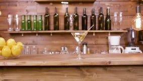 Ολισθαίνων ρυθμιστής που πυροβολείται ενός ποτηριού martini του ποτού σε ένα υπόβαθρο φραγμών απόθεμα βίντεο