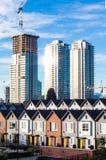 Ολοκαίνουργια townhouses σε μια σειρά τη φωτεινή ηλιόλουστη ημέρα με τα πολυόροφα κτίρια στο υπόβαθρο Στοκ Εικόνες