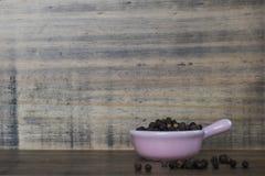 Ολόκληρα τα μαύρα βιετναμέζικα σε ένα μικροσκοπικό ρόδινο κεραμικό δοχείο σε έναν ξύλινους πίνακα και ένα υπόβαθρο στοκ εικόνα