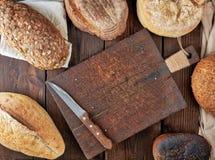 ολόκληρες φραντζόλες του ψωμιού φιαγμένου από άσπρες αλεύρι και σίκαλη σίτου με τους σπόρους στοκ εικόνες