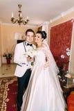 Ολόκληρη άποψη του όμορφου χαμόγελου παντρεμένου ακριβώς κρατώντας τη γαμήλια ανθοδέσμη Στοκ Εικόνες