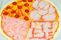Ολόκληρη μια πίτσα με τέσσερα διαφορετικά καλύμματα Στοκ Εικόνες