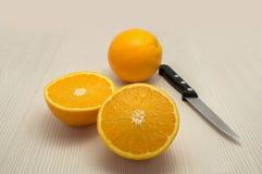 Ολόκληρο πορτοκάλι και μια αναχώρηση και ένα μαχαίρι Στοκ Φωτογραφία