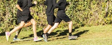 Ομάδα αγοριών που φορούν το μαύρο τρέξιμο στη χλόη Στοκ φωτογραφία με δικαίωμα ελεύθερης χρήσης