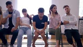 Ομάδα ανθρώπων με τις διαφορετικές συγκινήσεις που κάθεται στη σειρά στις καρέκλες μετά από τη συνεδρίαση της θεραπείας απόθεμα βίντεο