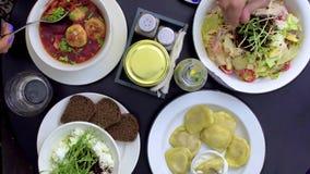 Ομάδα ανθρώπων που έχει το γεύμα στον πίνακα με τα τρόφιμα απόθεμα βίντεο