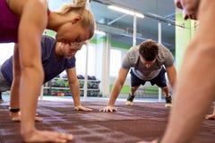 Ομάδα ανθρώπων που κάνει την ευθεία σανίδα βραχιόνων στη γυμναστική Στοκ Φωτογραφία