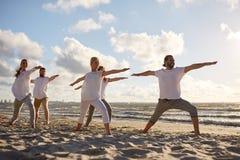 Ομάδα ανθρώπων που κάνει τις ασκήσεις γιόγκας στην παραλία Στοκ εικόνες με δικαίωμα ελεύθερης χρήσης