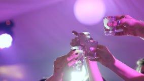 Ομάδα ανθρώπων που κατασκευάζει τη φρυγανιά με τα μικρά γυαλιά στο νυχτερινό κέντρο διασκέδασης στο υπόβαθρο των φω'των απόθεμα βίντεο