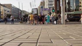 Ομάδα ανθρώπων που περπατά κατά μήκος της διάβασης πεζών μέσω της αστικής οδού φιλμ μικρού μήκους