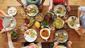 Ομάδα ανθρώπων που τρώει στον πίνακα με τα τρόφιμα απόθεμα βίντεο