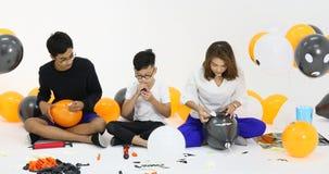 Ομάδα ανθρώπων στην οικογενειακή βοήθεια για να προετοιμάσει μαζί τα μπαλόνια του κόμματος αποκριών απόθεμα βίντεο
