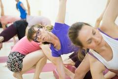 Ομάδα ανθρώπων positivel που ασκούν τη γιόγκα στη γυμναστική στοκ εικόνες