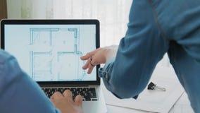 Ομάδα αρχιτεκτονικής που εργάζεται μαζί στο lap-top με τα σχεδιαγράμματα απόθεμα βίντεο