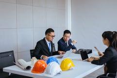 Ομάδα ασιατικών λαών αρχιτεκτόνων που συναντούν και που απασχολούνται στην επικοινωνία καθμένος στο γραφείο γραφείων δωματίων από στοκ φωτογραφία με δικαίωμα ελεύθερης χρήσης