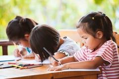 Ομάδα ασιατικών παιδιών που σύρουν και που χρωματίζουν με το κραγιόνι Στοκ φωτογραφία με δικαίωμα ελεύθερης χρήσης