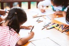 Ομάδα ασιατικών παιδιών που σύρουν και που χρωματίζουν με το κραγιόνι Στοκ εικόνα με δικαίωμα ελεύθερης χρήσης