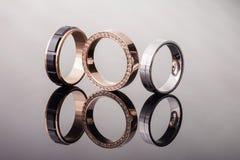 Ομάδα γαμήλιων δαχτυλιδιών των διαφορετικών μορφών με τα διαμάντια σε ένα στιλπνό υπόβαθρο, που απομονώνονται, κινηματογράφηση σε Στοκ Εικόνες